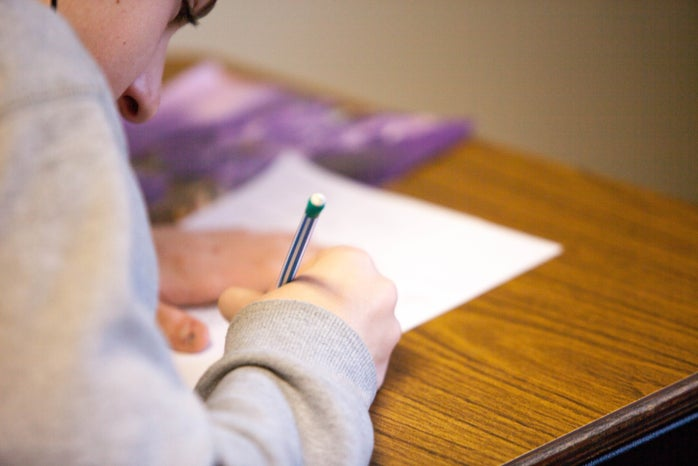 person holding pencil writing on paper