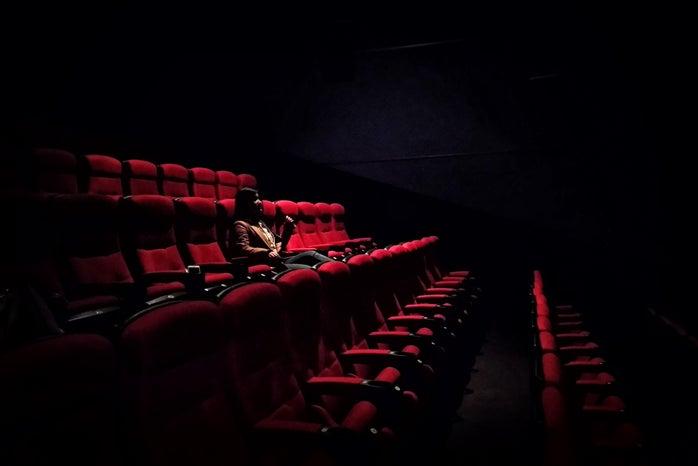 Woman sitting in dark movie theatre
