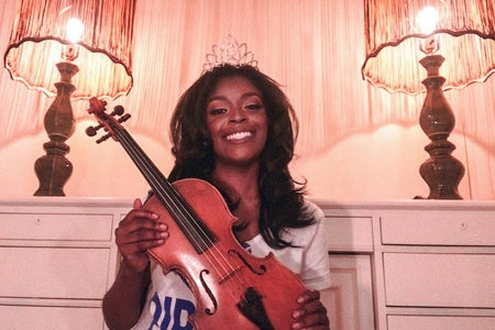 The new Miss Hampton holds up her violin