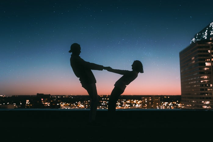 silhouette of people holding hands at sunset and leaning away from each other