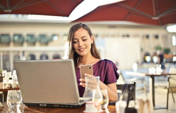 Woman sitting at a restaurant table outside on her phone with a laptop on the table in front of her.