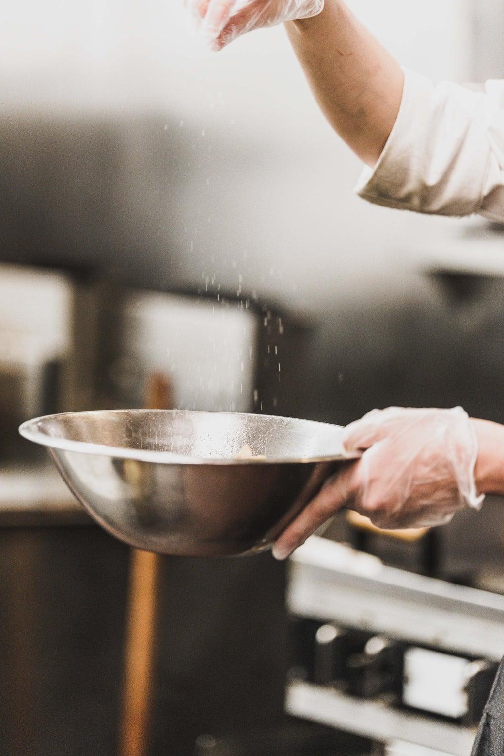 Chef pouring salt into a bowl