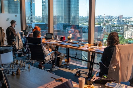 people sitting at a desk in front of a window