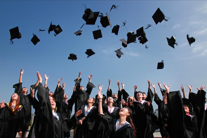 Female students throw their graduation caps in the air.
