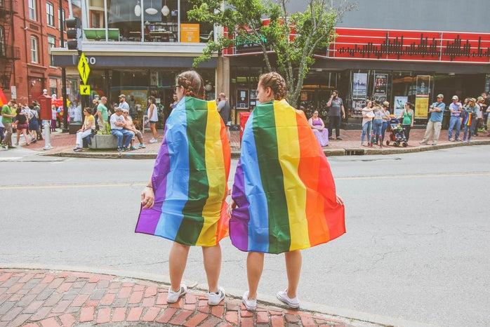 Two people wearing LGBTQ pride flags