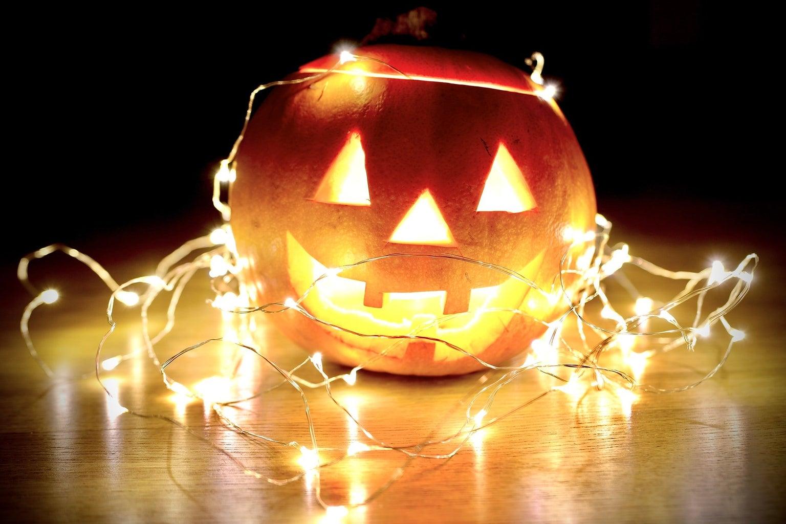 happy pumpkin wrapped in fairy lights