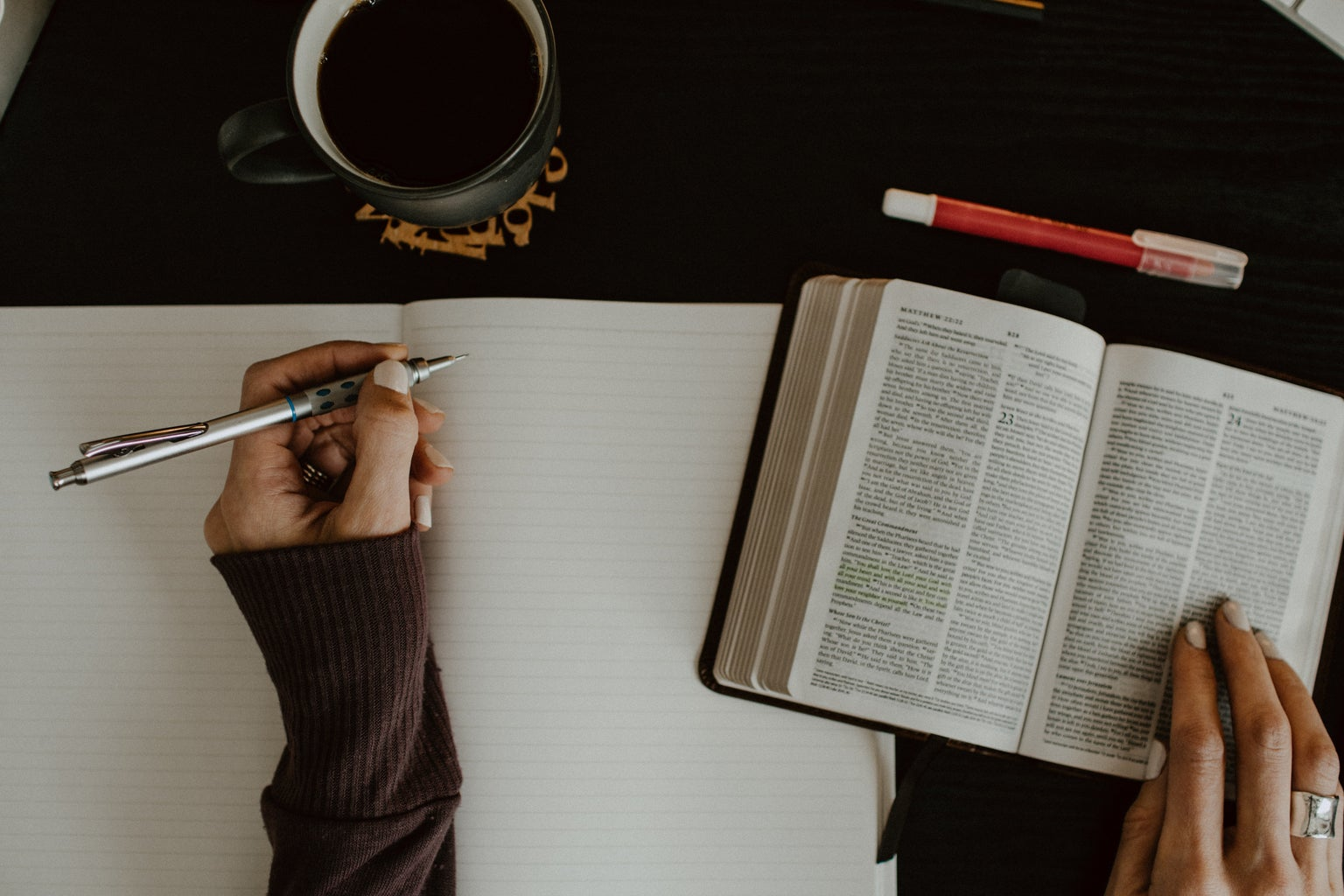 person writing in a journal while they read the bible