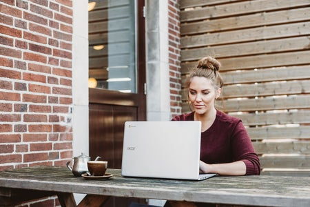 Woman working at laptop outside with coffee