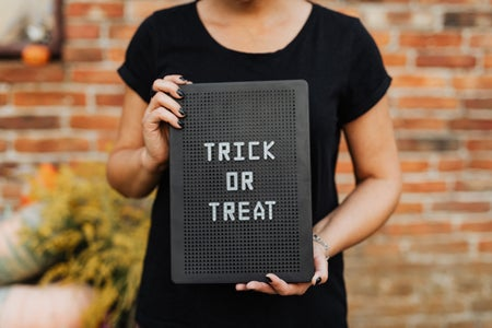 Person Holding a Trick or Treat Sign
