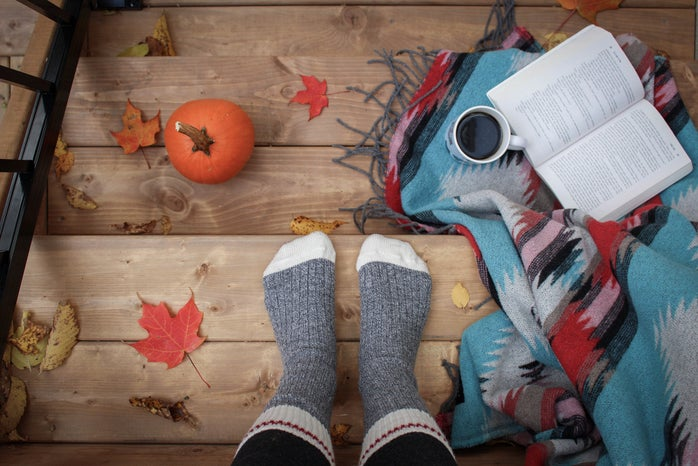 Socked feet with pumpkins, books, and leaves