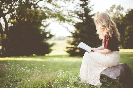 woman sitting in a field reading