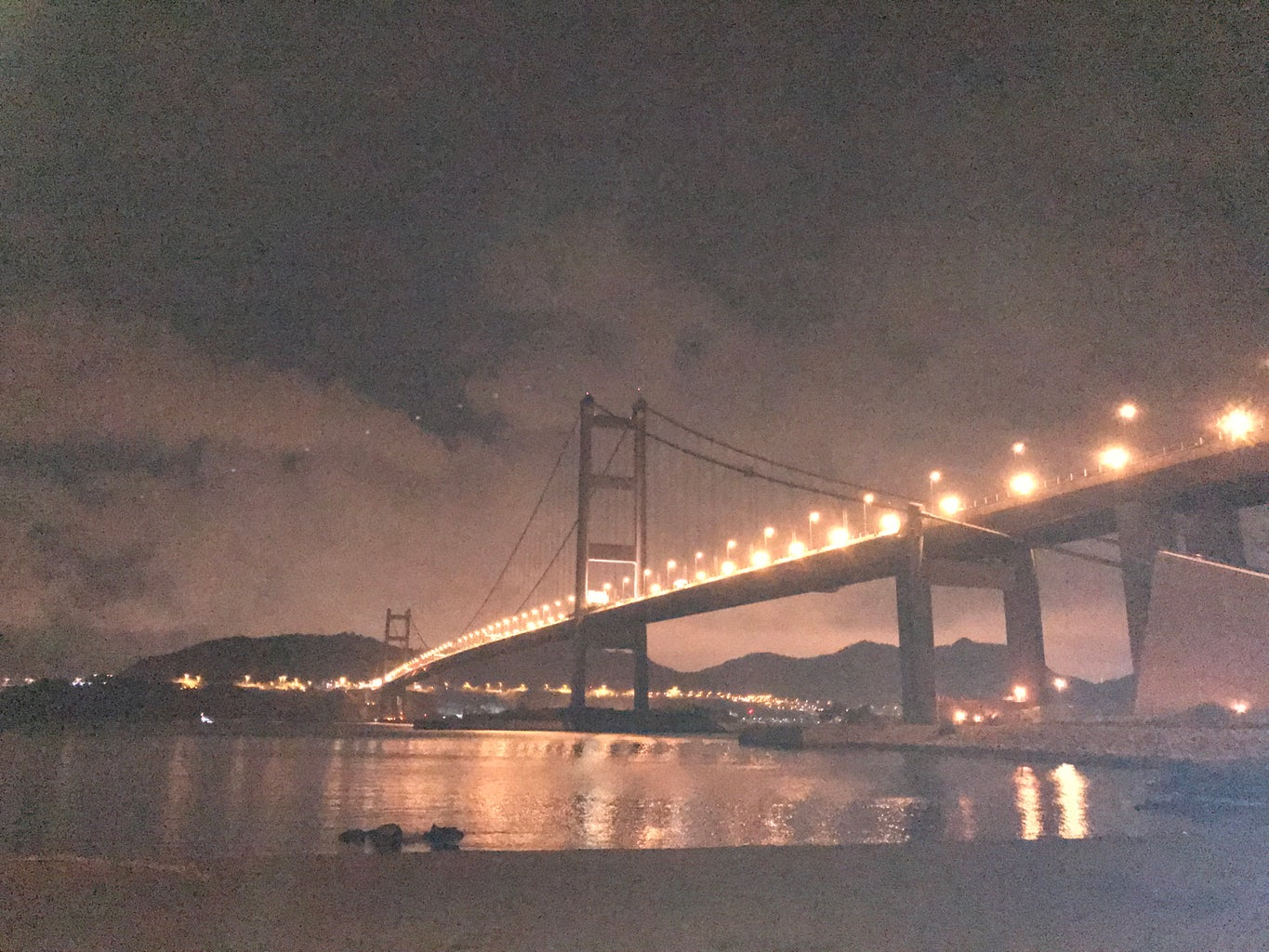 a beach next to a long, bright bridge at night, lights on the side of the bridge, city lights on the opposite side of the beach,