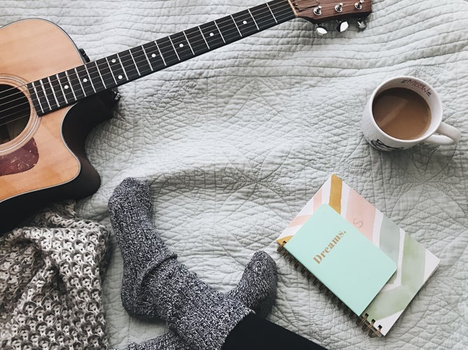 guitar, coffee, and journals laid on bed