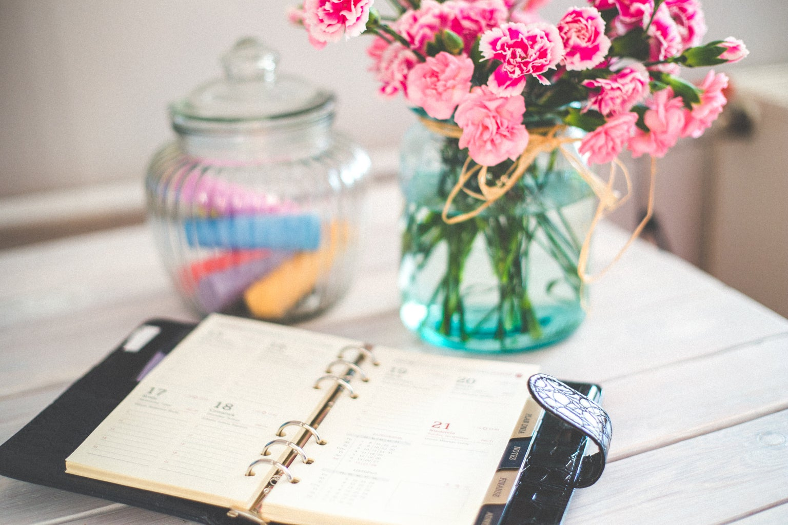 planner and pink flowers on desk