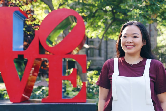 Young Asian woman, Jessica Bao, standing in front of the LOVE statue wearing a maroon shirt with white overalls.