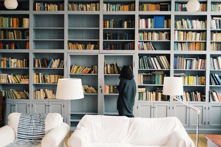 woman looking at a bookshelf