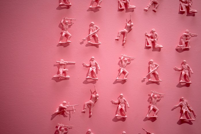 tiny pink toy soldiers on a pink wall