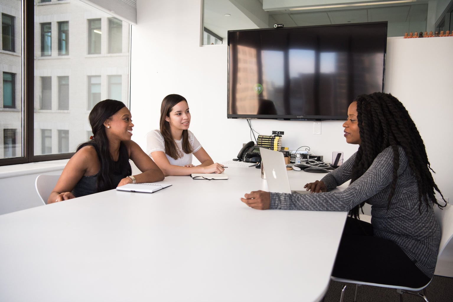 Three women of color are sitting at a table; two are on one side and  one is on the other with a laptop in front of her. They are in a conference room.