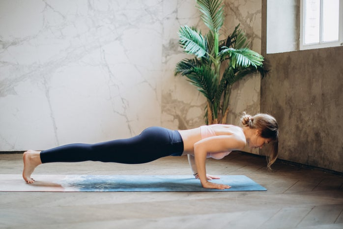 woman doing plank on yoga mat