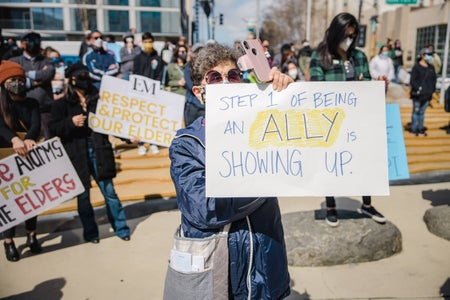 """elderly woman holding up signs that says """"step 1 of being an ally is showing up"""""""