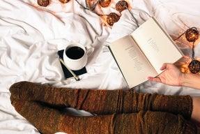 Mug of black coffee next to woman reading a book