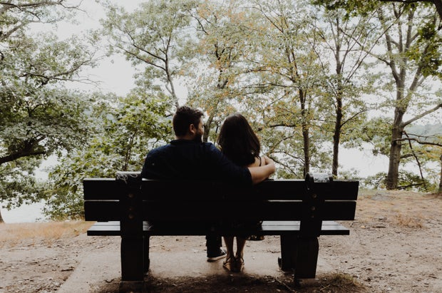 Couple talking on park bench