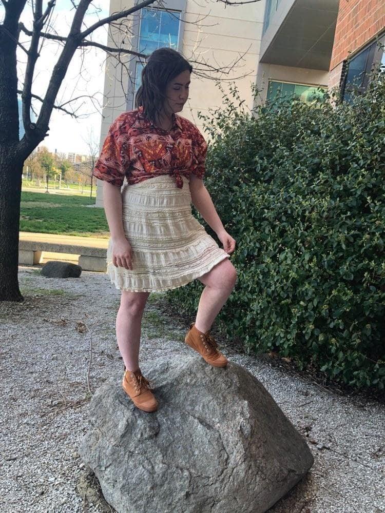 Girl in dress posing on a rock.