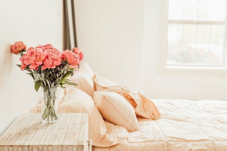 four orange pillows on a bed with flowers on the bedside table