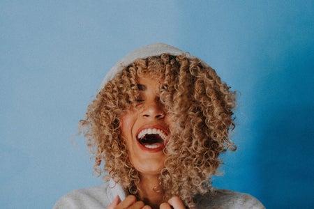woman in hoodie laughing