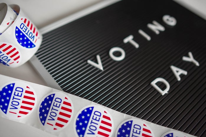 """sign that says """"voting day"""" with I voted stickers next to it"""
