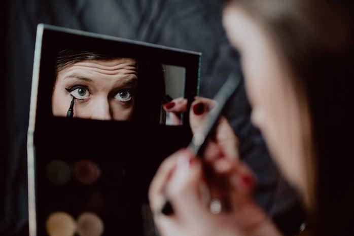 woman holding black framed mirror