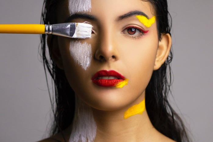 Woman with red lips with yellow and white paint on her face.