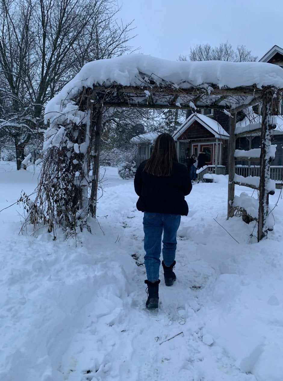 Girl walking in snow, view from behind, house in background. Pictured are Rachel Alter, Sasha Folgoas and Daphna Roytblat