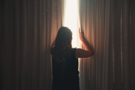 woman opening window curtain in shining daylight