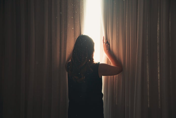 woman opening window curtain in shining daylight