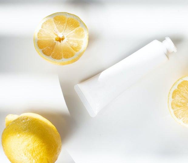 sliced lemons beside white container