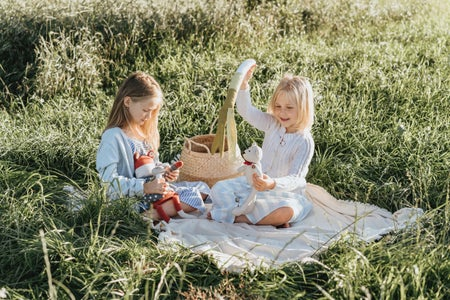 Two girls playing with dolls on a picnic blanket