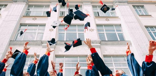 graduation caps thrown in air