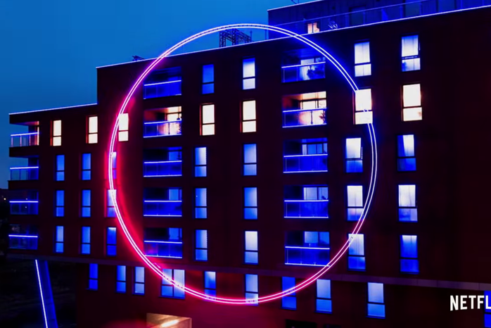Large glowing circle on the outside of a building from The Circle Official Trailer on YouTube by Netflix