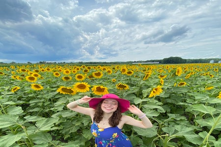 Camryn in a sunflower field with a pink hat