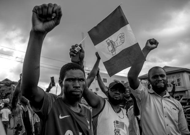 Nigerian men raising fists, protesting SARS