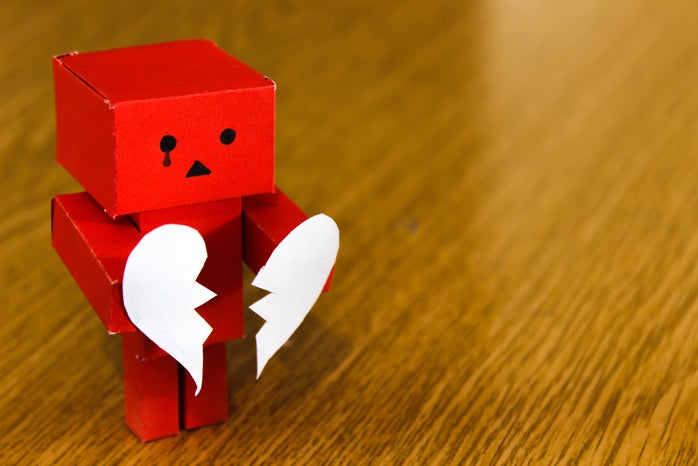 Red block figure holding a white broken heart