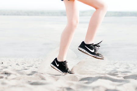 Woman Wearing Pair of Black Nike Running Shoes