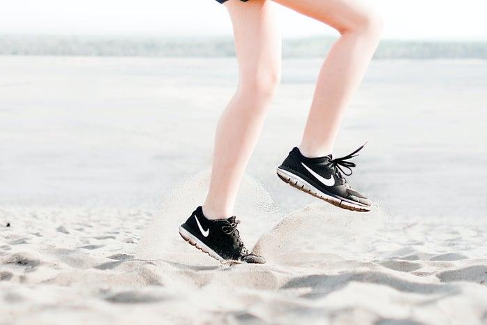 Woman Wearing Pair of Black Nike Running Shoes