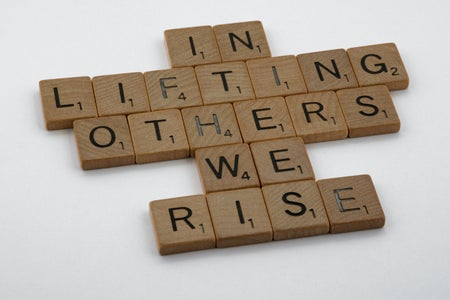 "scrabble letters on a white table that spell out ""in lifting others we rise"""
