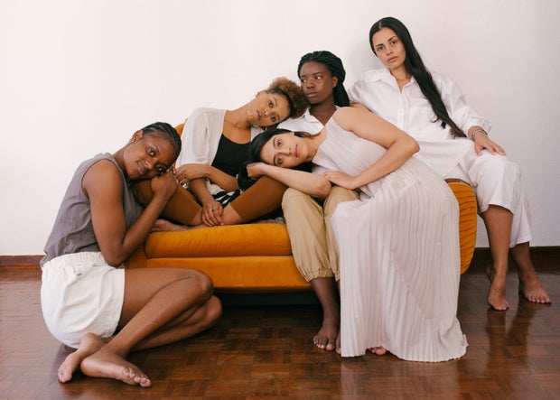 five women sitting on or around an orange couch