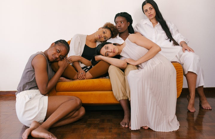 five women sitting on or around an orange couch
