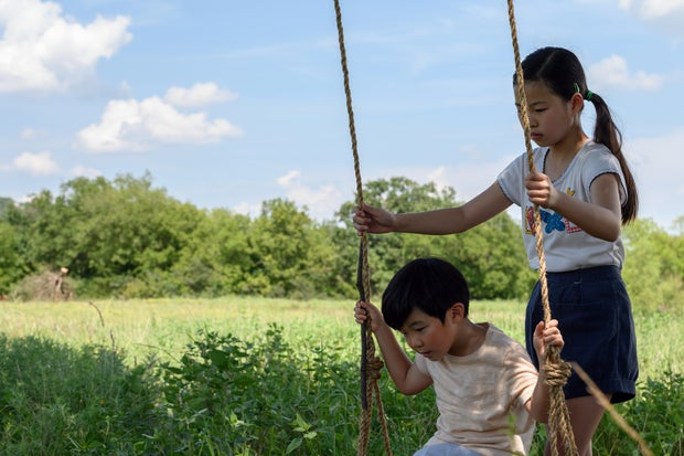 Anne Yi (Noel Cho) pushing her brother David (Alan S. Kim) on a swing.