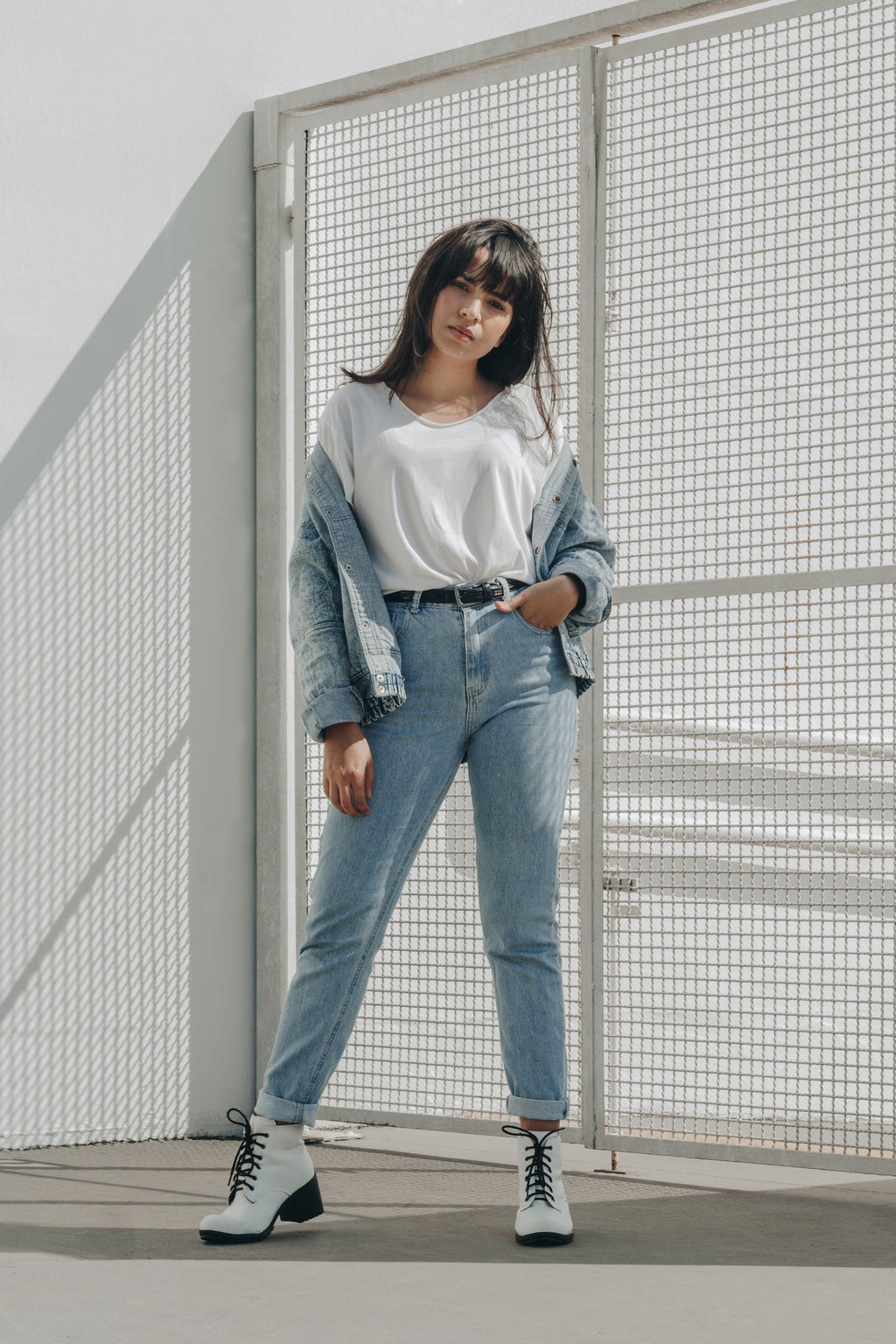 woman in white shirt and jeans in front of white wire fence