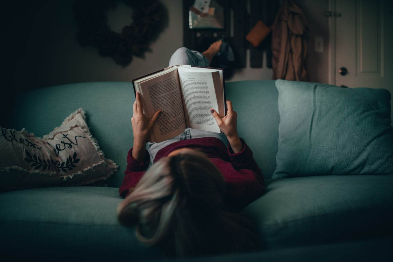 A woman reading on a couch.